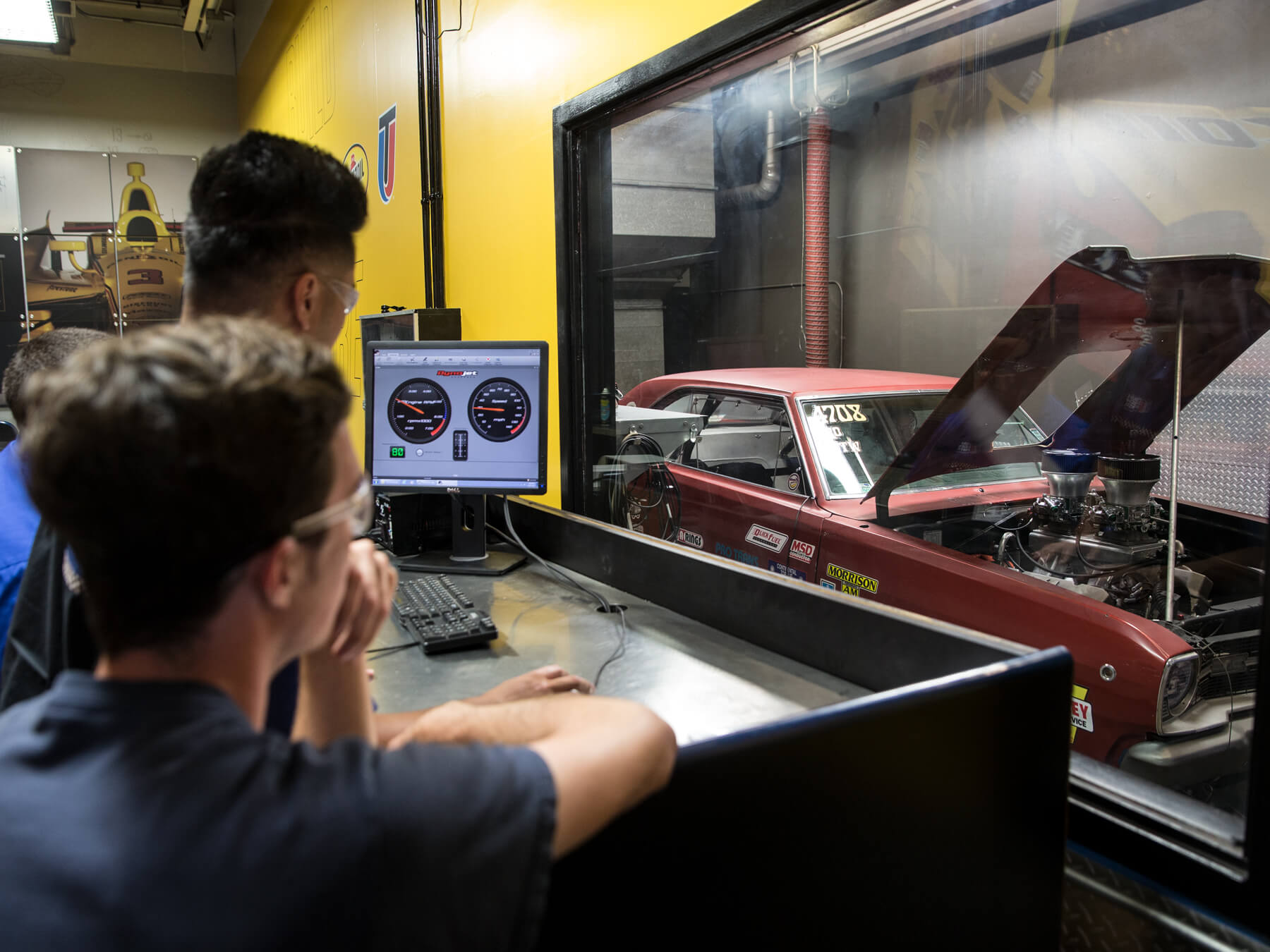 Students looking at a computer behind the glass in the Dyno lab