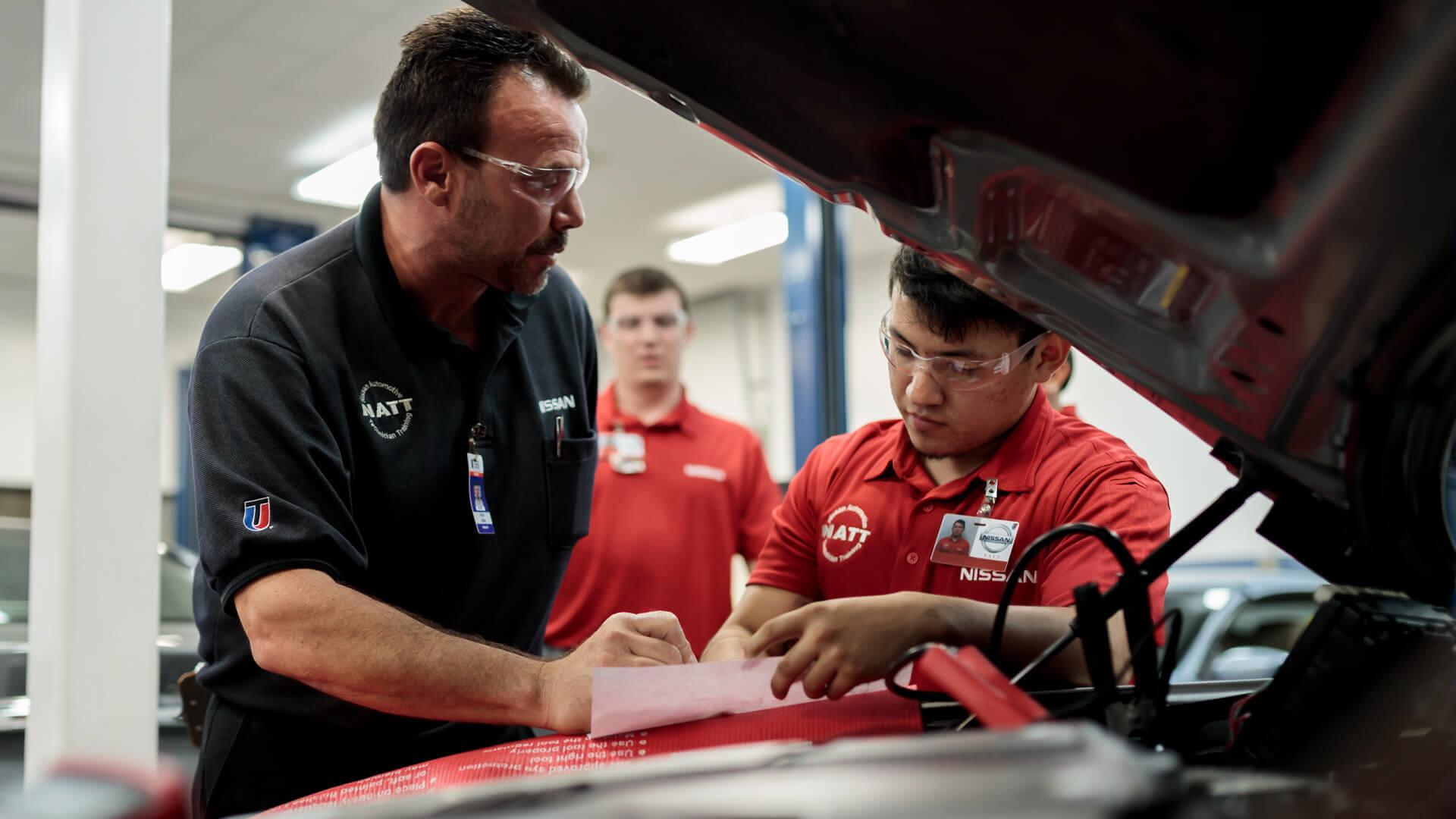 UTI Students and instructor working on the hood in the Nissan lab